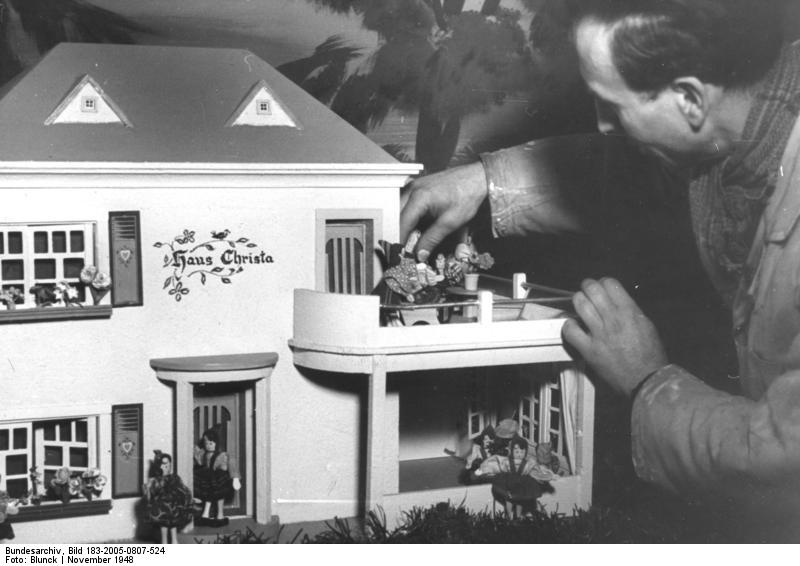Man adjusting dolls on Schönherr dolls house in 1948 photo from German National Archives