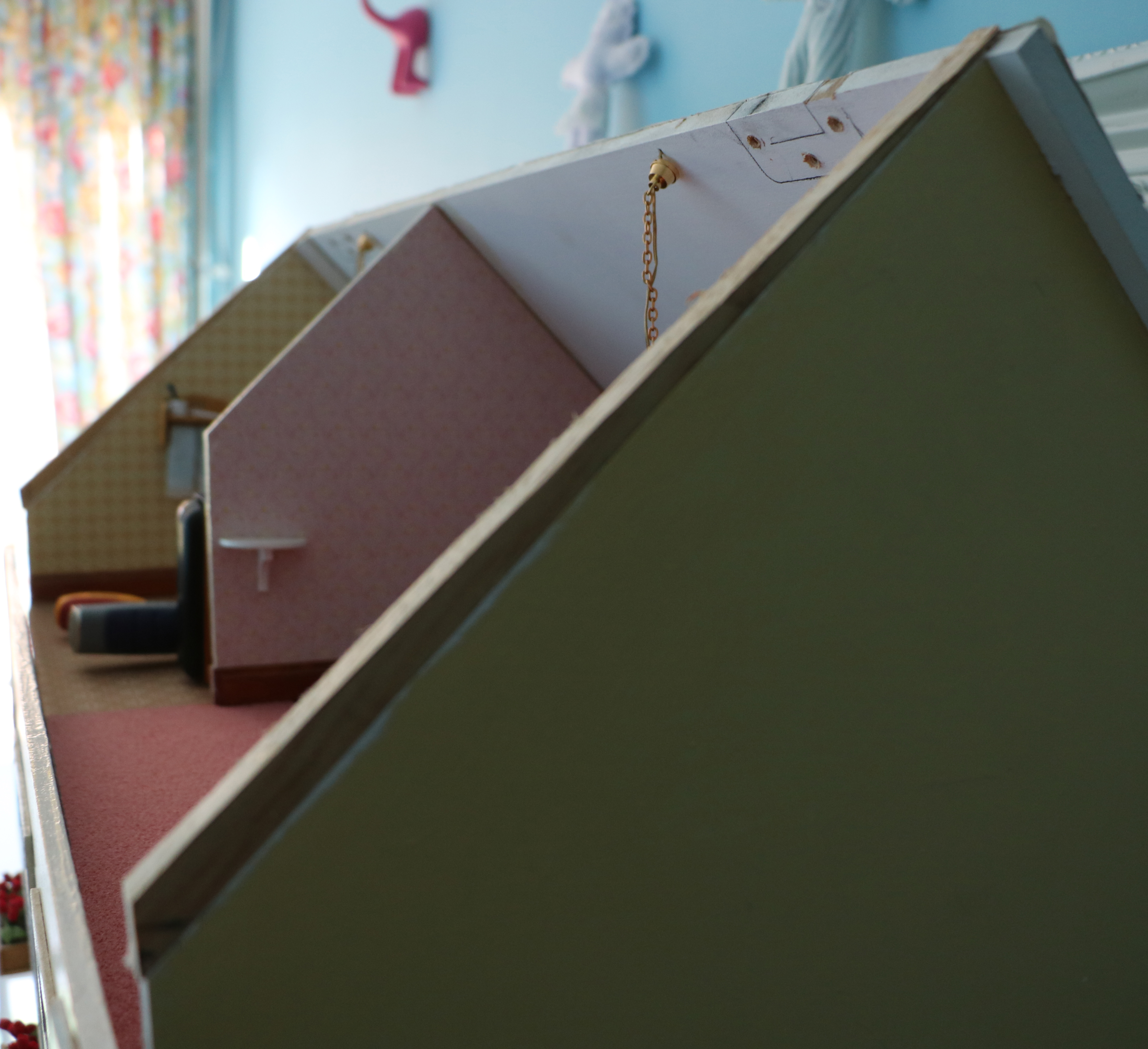 Side of dolls house showing extra piece of wood added on pitched top