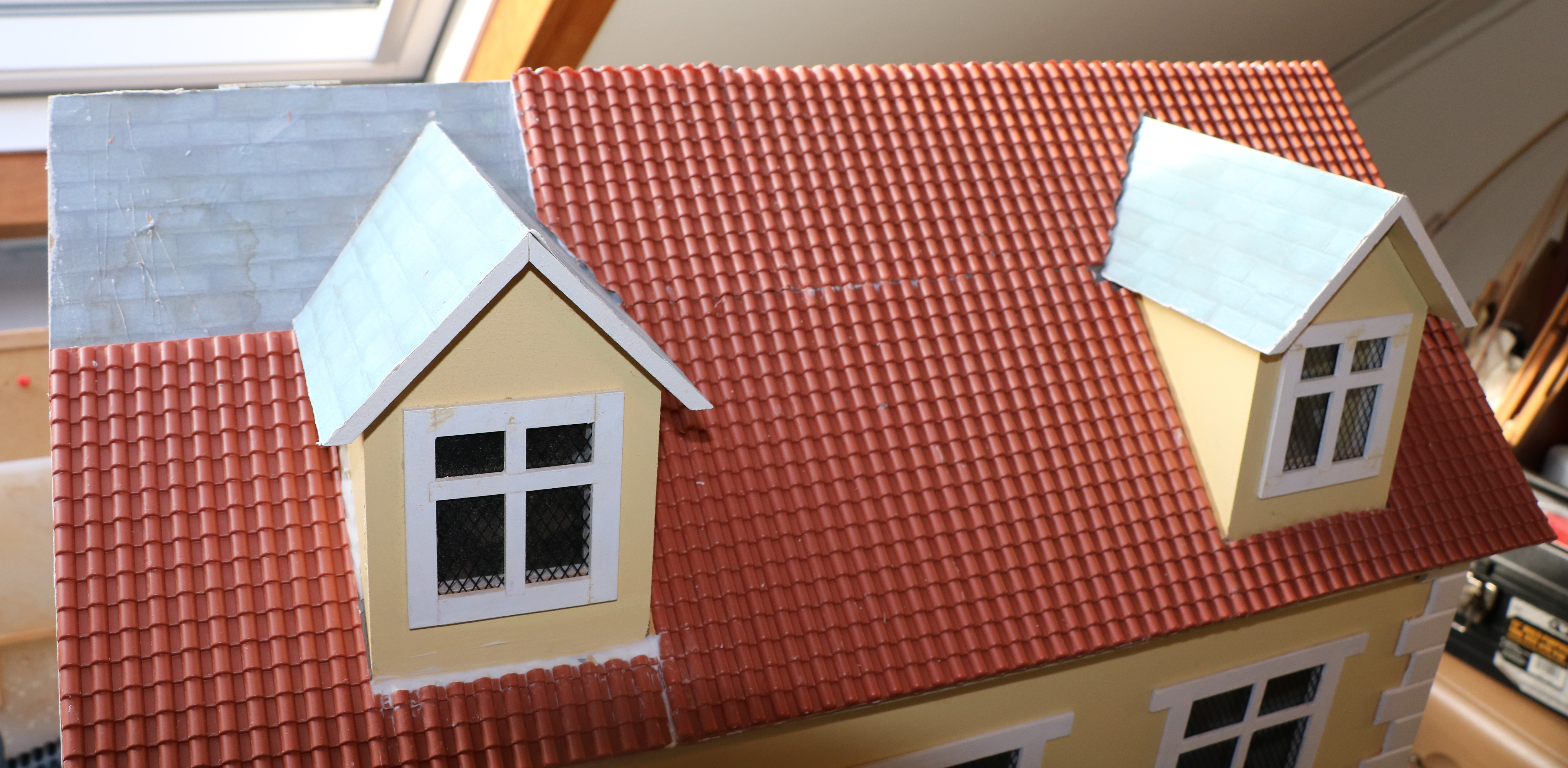 Roof of dolls house partly covered with sheets of tiling
