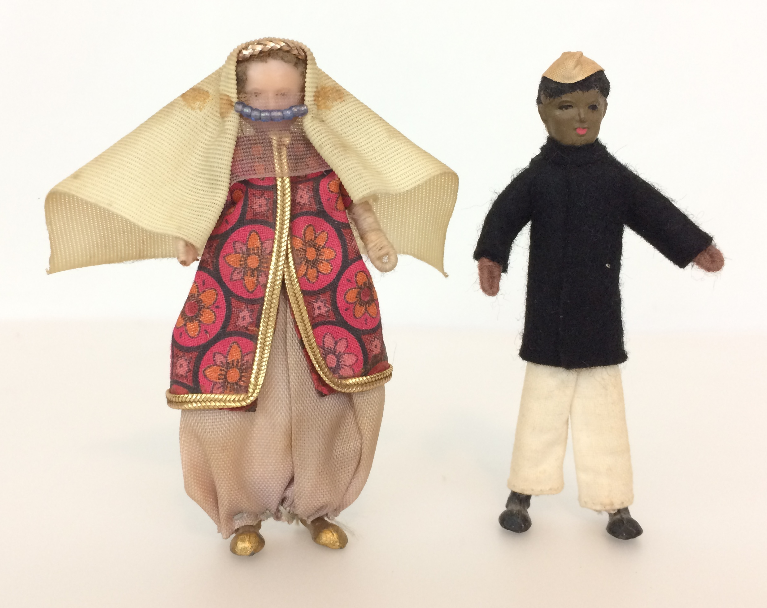 Doltoi dolls dressed in national costume, woman wearing a yashmak and man wearing a topi cap