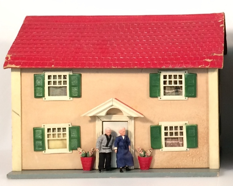 Schoenhut dolls house shown on left in photo above, with centered front door and four rooms
