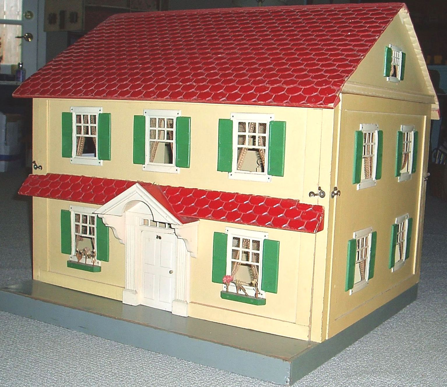 8 room Schoenhut dollhouse with front similar to previous house, taken at angle showing front and one side to show double depth of house