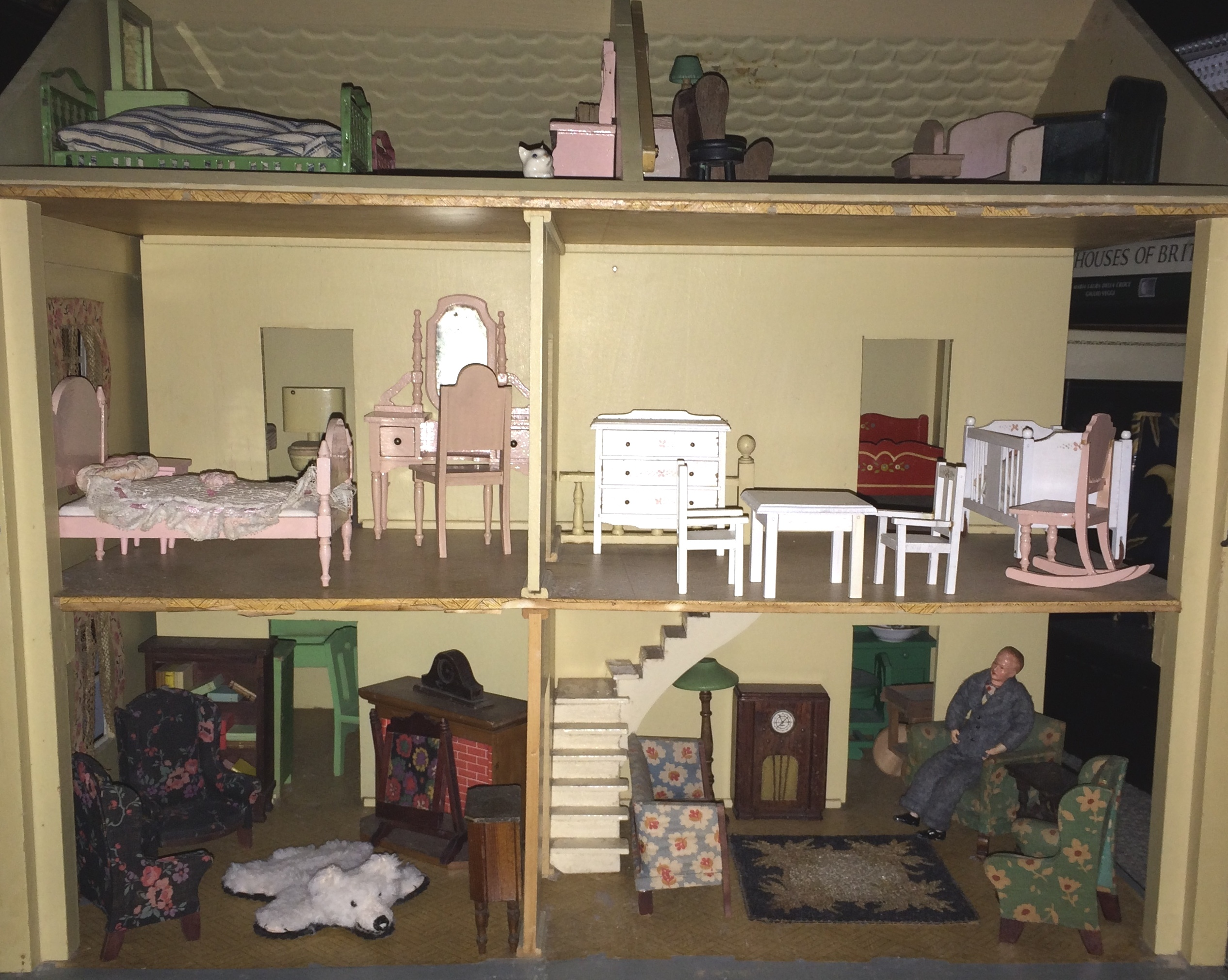 Interior of fromt of 8 room house, showing furnished living rooms (one with stairs) and bedrooms