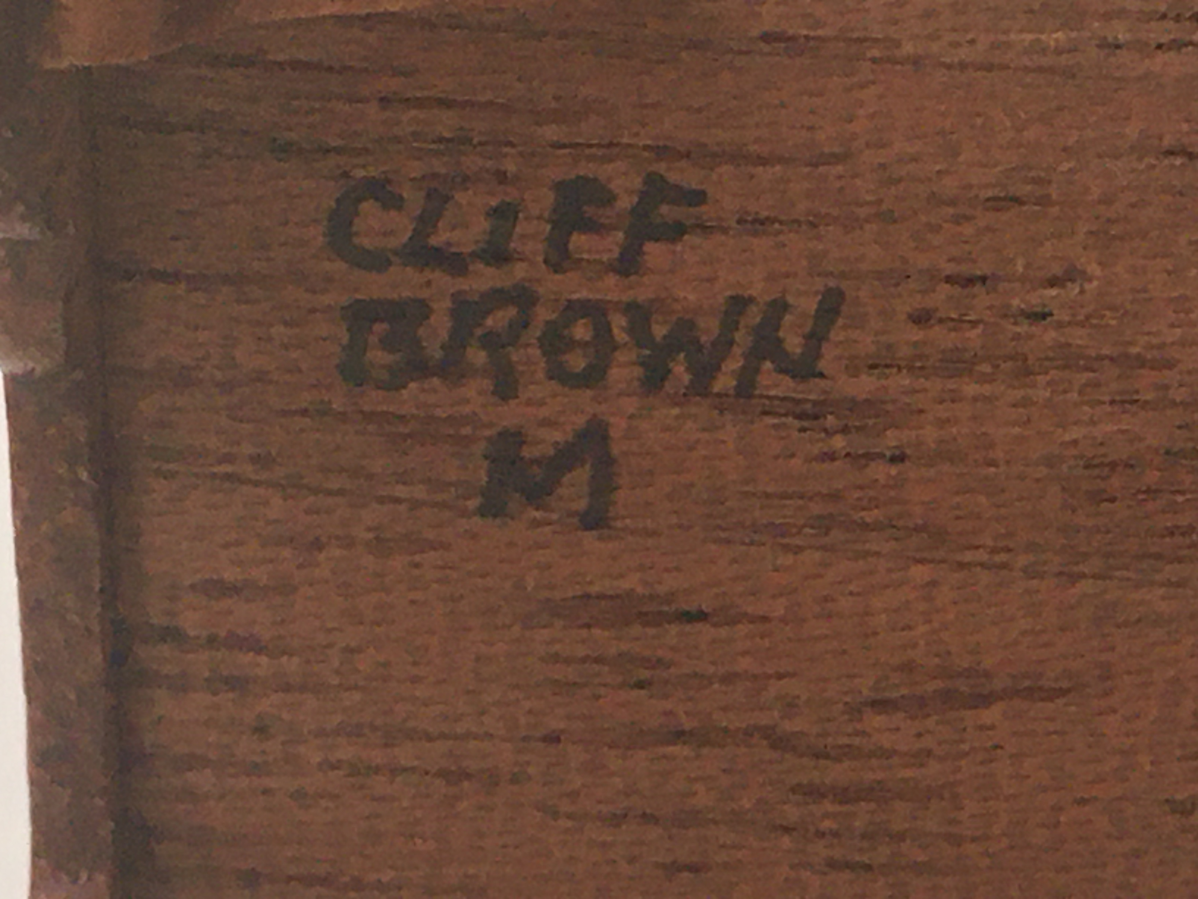A piece of furniture signed 'Cliff Brown' and the letter 'M' on the base in black ink and in capitals.