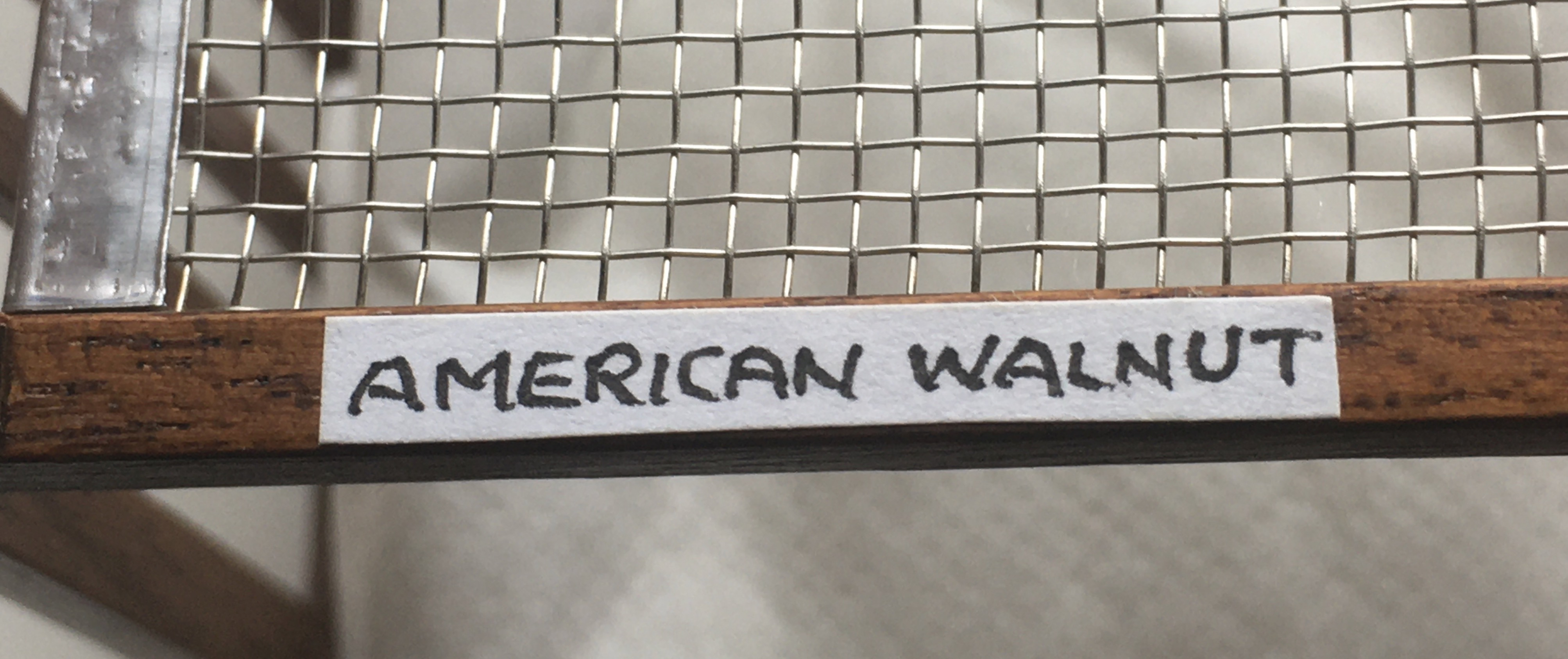 A white sticker, on the underside of the same bed as in the previous photo, reading 'American Walnut' in black ink and in capitals.